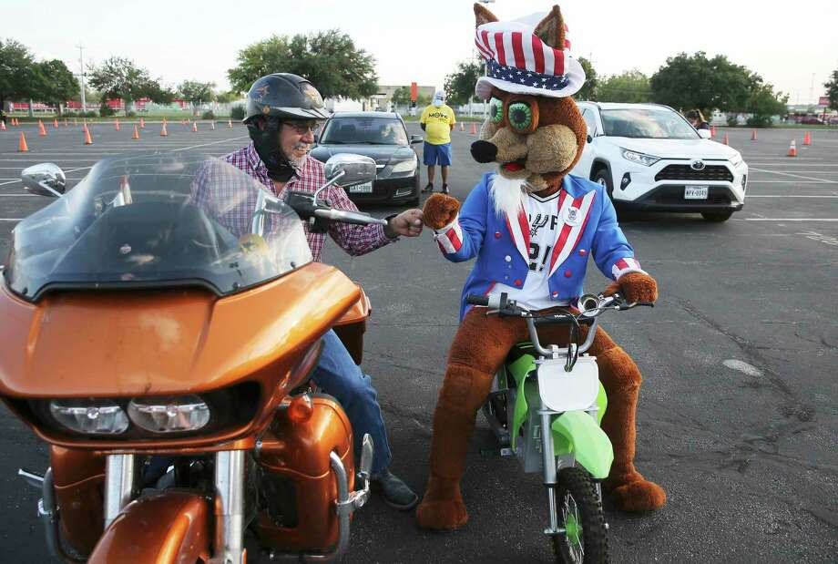 """Victor Flores (left) gets a fist bump with the Spurs Coyote as Spurs Sports & Entertainment and non-partisan non-profit MOVE Texas team up for a voter registration drive on Tuesday, Sept. 15, 2020. Volunteers and motorists lined up early Tuesday evening on the grounds of the AT&T Center to fill out voter registration forms. New voters remained in their cars as volunteers helped walk them through the voter registration process. The Spurs Coyote joined and greeted people as they filled out the paperwork. As a treat for those who came out to register, the Spurs championship trophies were on display for photographs as well as a commemorative """"Vote"""" t-shirt was available. Photo: Kin Man Hui, San Antonio Express-News / Staff Photographer / **MANDATORY CREDIT FOR PHOTOGRAPHER AND SAN ANTONIO EXPRESS-NEWS/NO SALES/MAGS OUT/ TV OUT"""