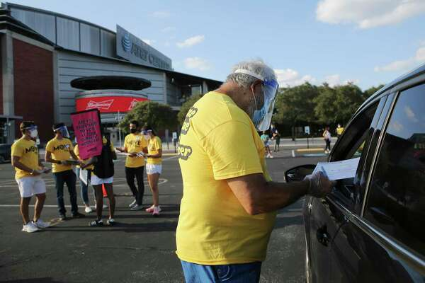 """Don Kahn (center) helps an individual fill out registration paperwork as Spurs Sports & Entertainment and non-partisan non-profit MOVE Texas team up for a voter registration drive on Tuesday, Sept. 15, 2020. Volunteers and motorists lined up early Tuesday evening on the grounds of the AT&T Center to fill out voter registration forms. New voters remained in their cars as volunteers helped walk them through the voter registration process. The Spurs Coyote joined and greeted people as they filled out the paperwork. As a treat for those who came out to register, the Spurs championship trophies were on display for photographs as well as a commemorative """"Vote"""" t-shirt was available."""