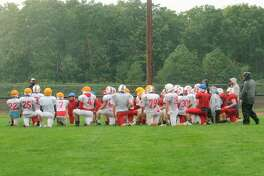 Benzie Central's football team meets at the conclusion of a rainy practice on Saturday. (Photo/Robert Myers)