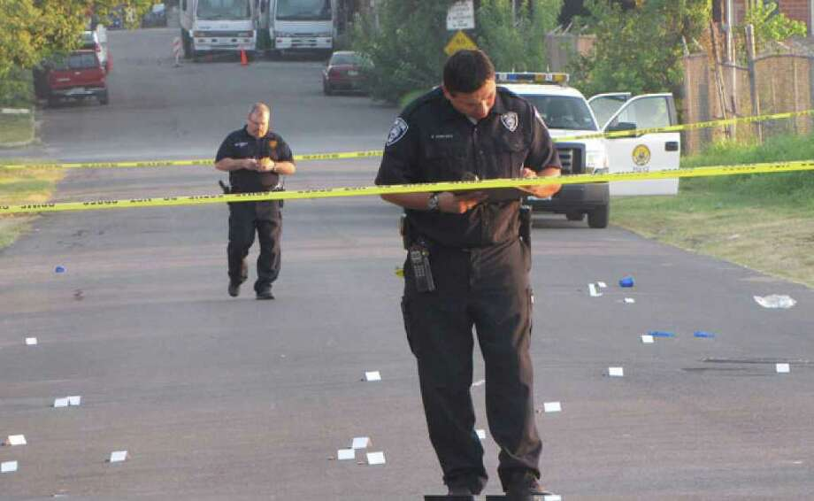: San Antonio police photograph dozens of shell casings that litter an East Side street where two men were fatally shot and several others were injured early Sunday morning.