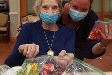 Candlewood Valley Health & Rehab resident Jane Palmer and Recreation Director Kathleen Horvath tie-dye face masks together.