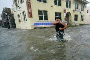 Trent Airhart wades through flood waters, Wednesday, Sept. 16, 2020, in downtown Pensacola, Fla. Hurricane Sally made landfall Wednesday near Gulf Shores, Alabama, as a Category 2 storm, pushing a surge of ocean water onto the coast and dumping torrential rain that forecasters said would cause dangerous flooding from the Florida Panhandle to Mississippi and well inland in the days ahead.