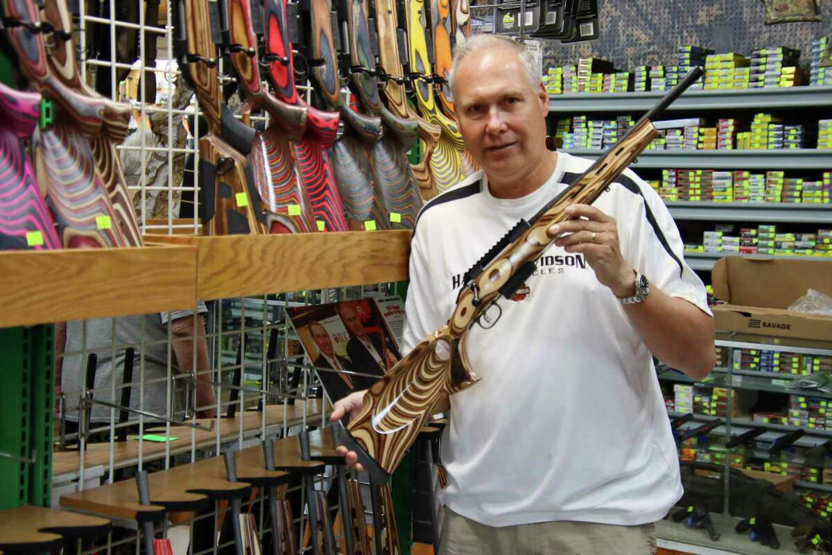 Randy Brown, owner of Randy's Hunting Center in Bad Axe, holds one of severallaminated stock rifles he has in his inventory. (Scott Nunn/Huron Daily Tribune)