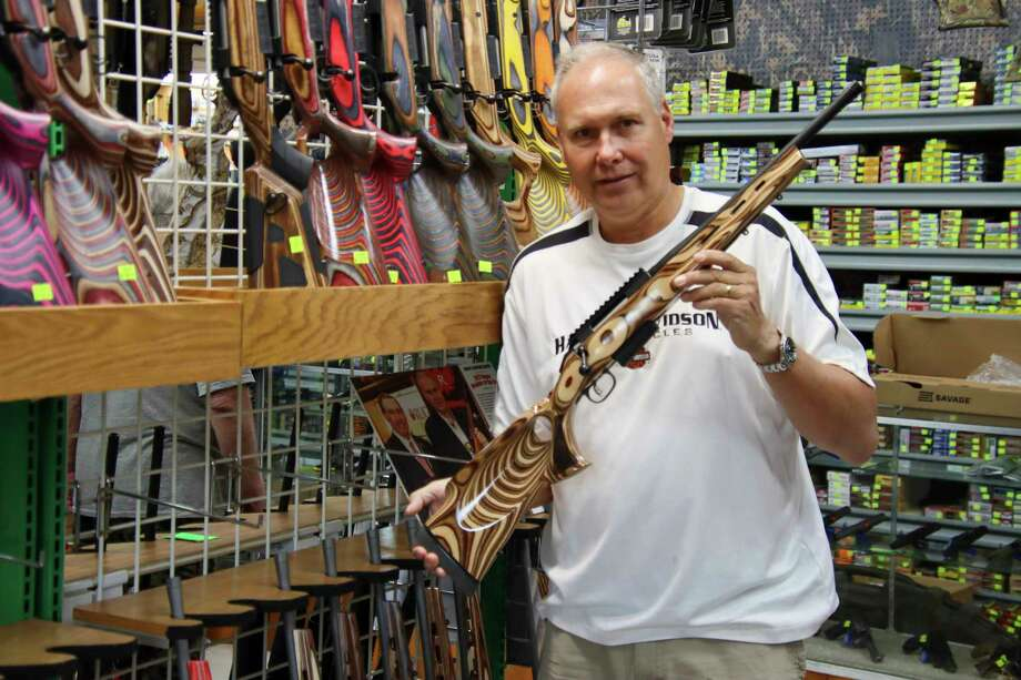 Randy Brown, owner of Randy's Hunting Center in Bad Axe, holds one of several laminated stock rifles he has in his inventory. (Scott Nunn/Huron Daily Tribune)