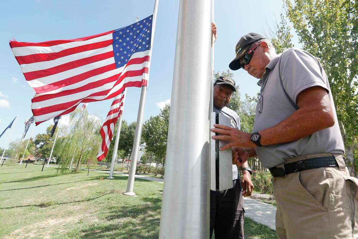 U.S. Army veterans Henry Calven, center, and Floyd Stewart lower flags at the Montgomery County Veterans Memorial Park in honor of Mayor Toby Powell, Tuesday, Sept. 15, 2020, in Conroe. Gov. Greg Abbott ordered the lowering of both the American and Texas flags to half-staff in honor of Powell, 79, who passed away Saturday following a lengthy battle with cancer.