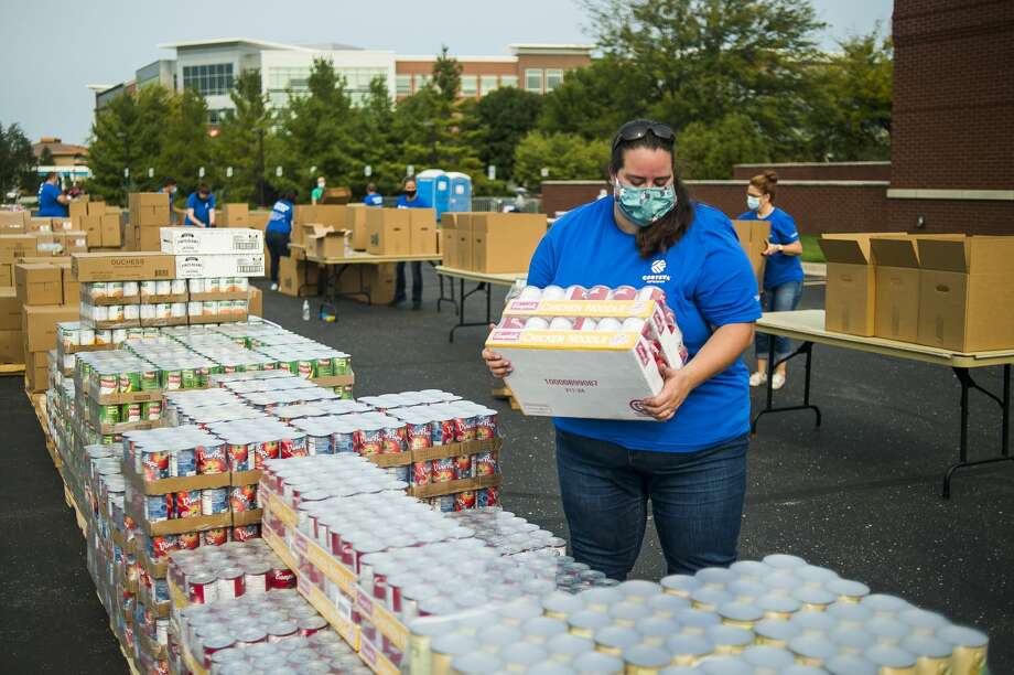 Corteva Agrisciences employee Bethany Duquette loads cans of soup into boxes as over 100 volunteers work to pack more than 40,000 pounds of food into boxes for residents of Midland County Wednesday, Sept. 16, 2020 at Dow Diamond. The event was organized through a partnership between Corteva, United Way of Midland County and the Great Lakes Loons. (Katy Kildee/kkildee@mdn.net) Photo: (Katy Kildee/kkildee@mdn.net)