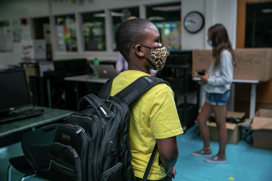 A student waits to receive a Chromebook at Rippowam Middle School on September 14, 2020 in Stamford, Connecticut. 