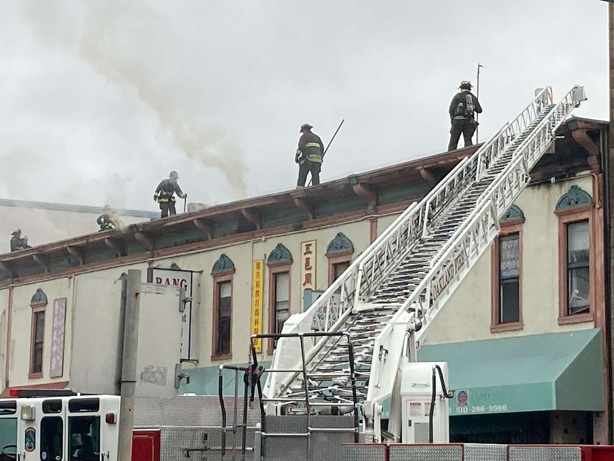 Firefighters on the roof of a Webster Street building battling a massive five-alarm blaze in Oakland's Chinatown neighborhood Sept. 16, 2020