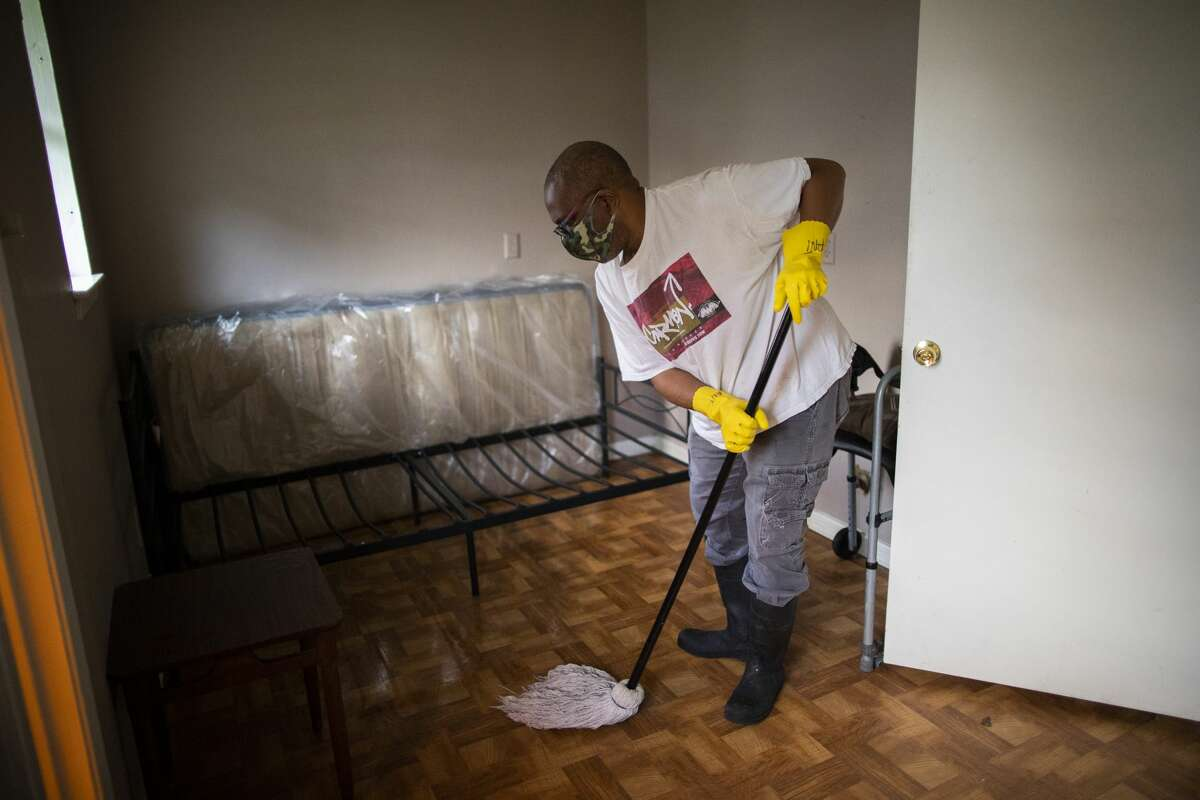 Jacob's Home for Men's owner Anthony Frazier mops the room of a resident of the boarding home in Sunnyside on June 3, in Houston.