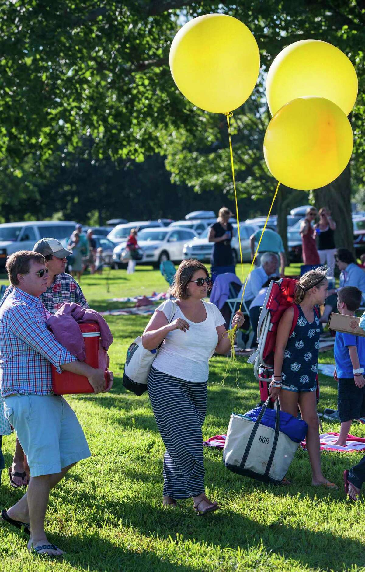 Jennifer Hladick, (center) a New Canaan resident, walks past other people at the town's annual Family Fourth event during a previous year of the celebration, with some balloons that she brought to it so that her friends could find her group at it. Hladick has been appointed to the town's Human Services Commission for a term that ends next December 2021.