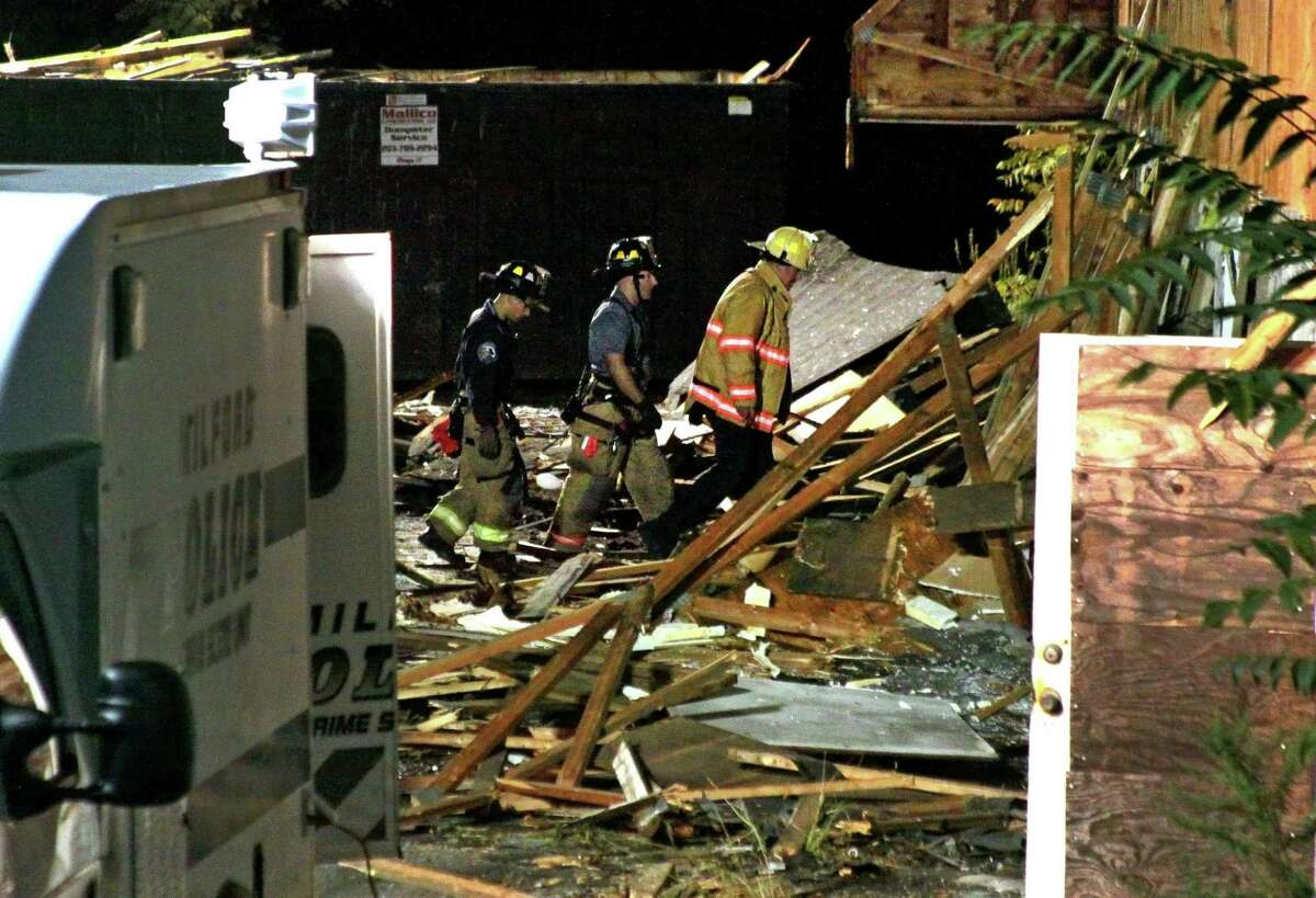 Milford firefighters sift through rubble near where a body was found inside an abandoned shopping plaza along Roses Mill Road in Milford, Conn., on Tuesday Sept. 15, 2020.