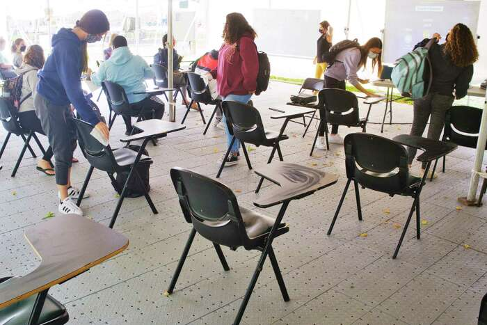 Siena College students disinfect the desks they were sitting at as a class held outdoors ends on Wednesday, September 16, 2020, in Loudonville, N.Y. (Paul Buckowski/Times Union)