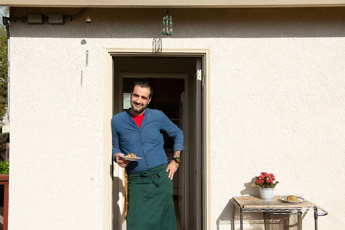 Hanif Sadr, chef and founder of the Northern Iranian pop-up Komaaj, poses for a portrait with an edible Haft Seen salad featuring apples as well as a few other symbolic items at his home on February 7, 2020 in El Cerrito, Calif.