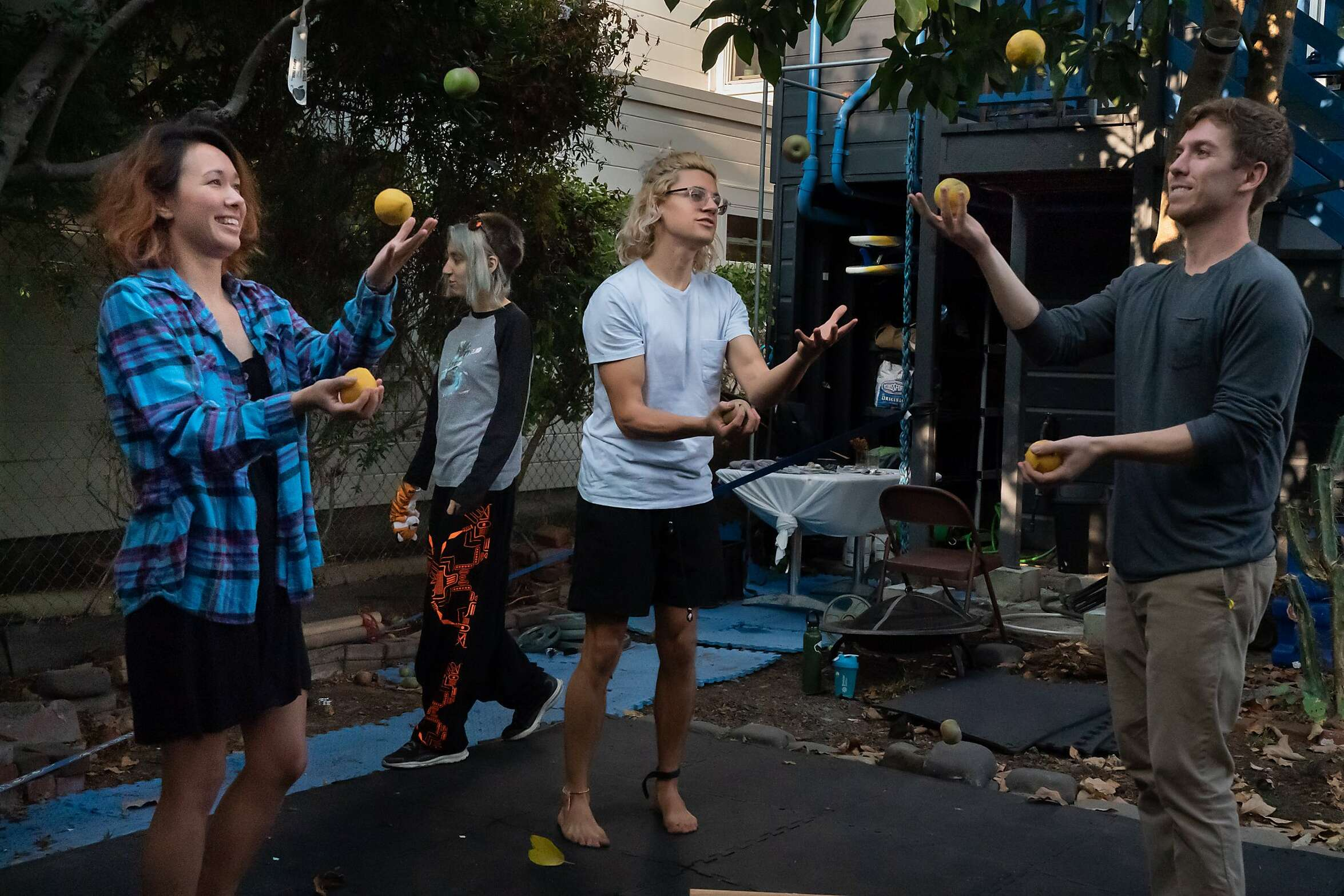 Caitlyn Kenney, Simon Wisdom and Armand Matossian juggle as Ninoa Knangar walks by at the Manor of Being House on Tuesday, Sept. 15, 2020 in San Francisco, Calif. Eleven international people share the home with occupations that includes tech, mathematics, music and art.