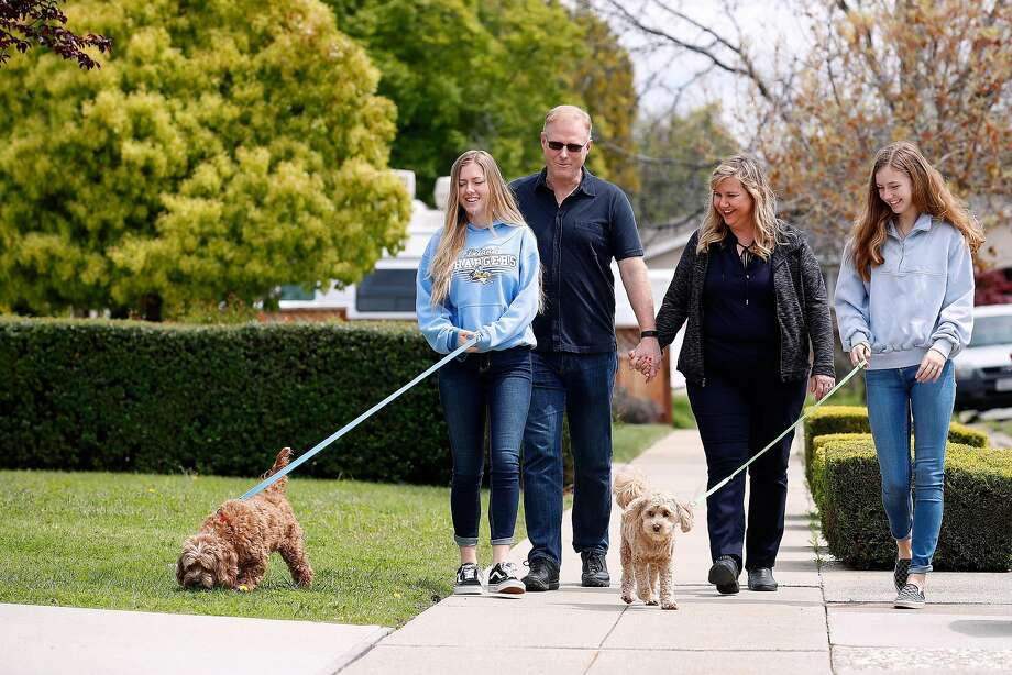 """(Left-right) Daughter Sarah McKinney,18, who walks pet Toby, dad Rick McKinney, Rosemary Pathy-McKinney, and daughter Sabrina McKinney, 15, who walks pet Stanley,  go for an afternoon walk in their neighborhood in San Jose,California on April 8, 2020.  Rosemary Pathy-McKinney, is a San Jose schoolteacher who was on her way into brains surgery for a tumor at UCSF Parnassus on March 15 when the surgery was abruptly postponed because it was deemed """"elective."""" The surgery ward was being prepared to only treat COVID patients who have still not materialized. Photo: Josie Lepe / Special To The Chronicle"""