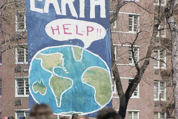 A crowd of people gather near a large poster that shows a speach bubble from planet Earth that reads 'Help!!,' on the first Earth Day conservation awareness celebration, New York, New York, April 22, 1970. (Hulton Archive/Getty Images/TNS)
