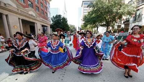 Dancers with Adrian Garcia's float walk down the street during the Houston Fiestas Patrias Parade downtown, celebrating the Mexican Independence Day, Saturday, Sept. 14, 2019, in Houston.