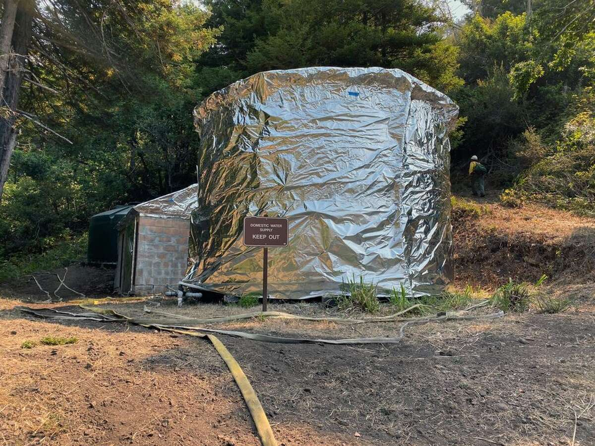 Officials wrap structures at Limekiln State Park on Sept. 7, 2020, to protect buildings and infrastructure from the Dolan Fire burning along California's Big Sur Coast.