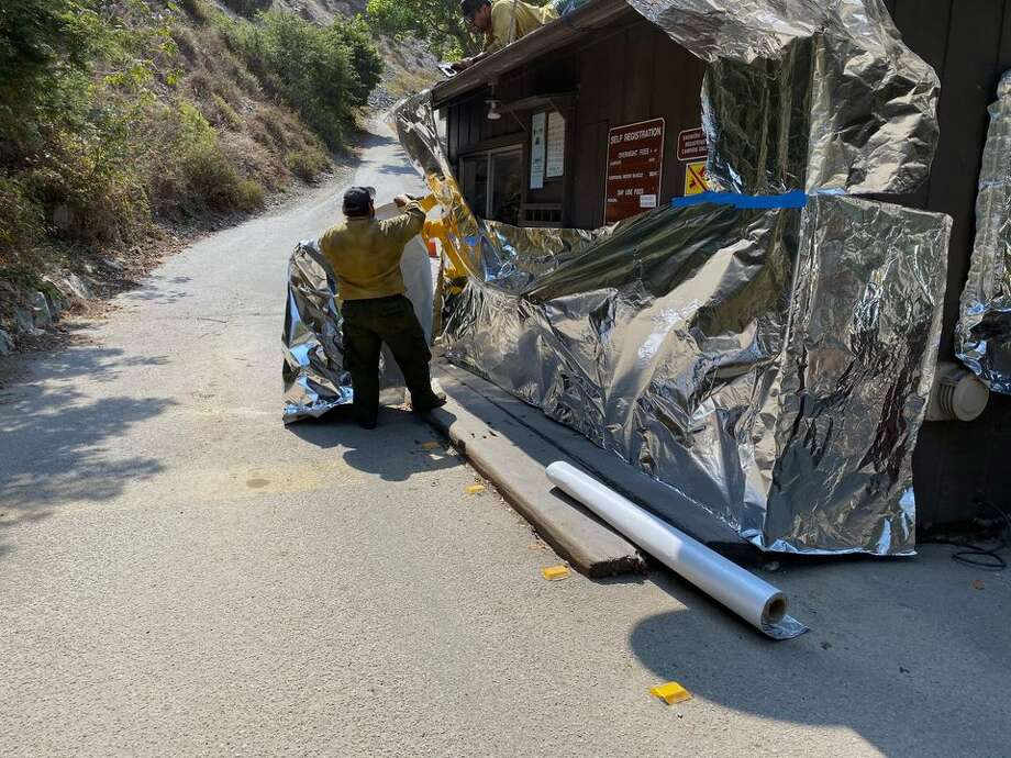 Officials wrap structures at Limekiln State Park on Sept. 7, 2020, to protect buildings and infrastructure from the Dolan Fire burning along California's Big Sur Coast. Photo: California State Parks