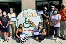 Carrie Picard, center, ECAD's marketing director and president of the newly adopted Connecticut ECAD Lions Club Branch, along with two Service Dogs in Training, welcome members of the Barkhamsted and Terryville Lions Clubs at ECAD's Training and Wellness Center in Winchester.