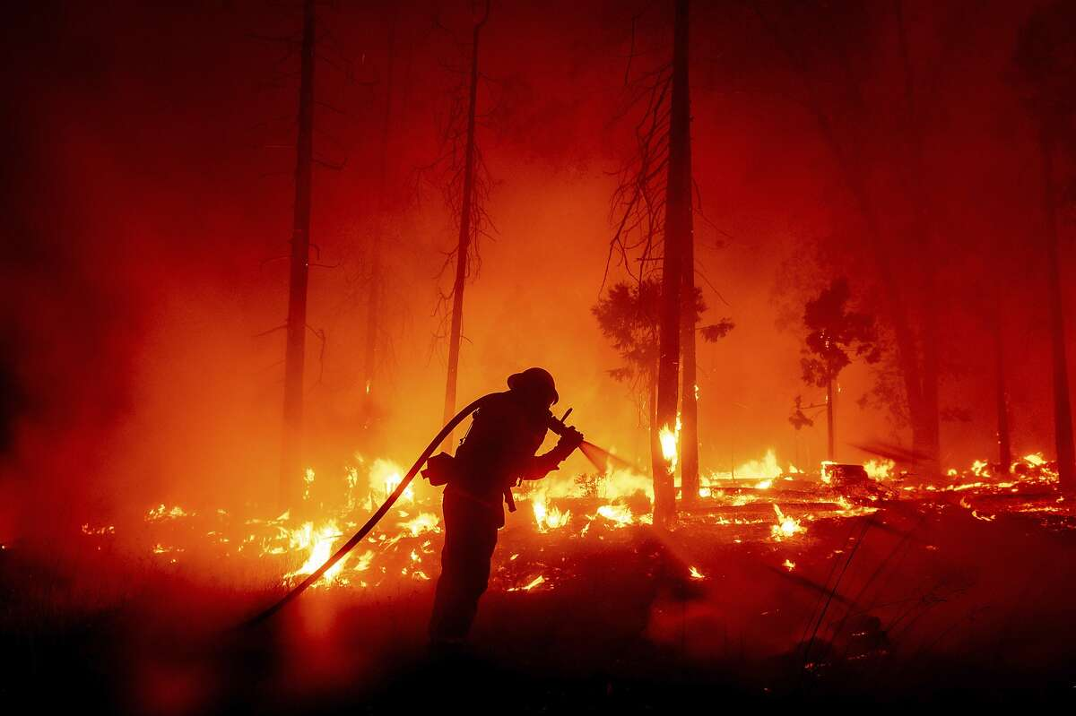 A firefighter battles the Creek Fire as it threatens homes in the Cascadel Woods neighborhood of Madera County, Calif., in September 2020.