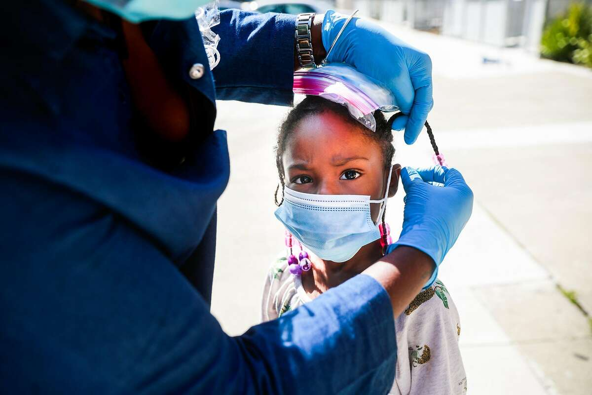 (L-r) Janice Smith helps London Gilbert, 5 put on her mask on Thursday, May 7, 2020 in San Francisco, California. The Community Resilience Caravans, which were organized through the city, canvassed neighborhoods throughout District 10 to encourage social distancing and hand out masks amid the coronavirus pandemic.