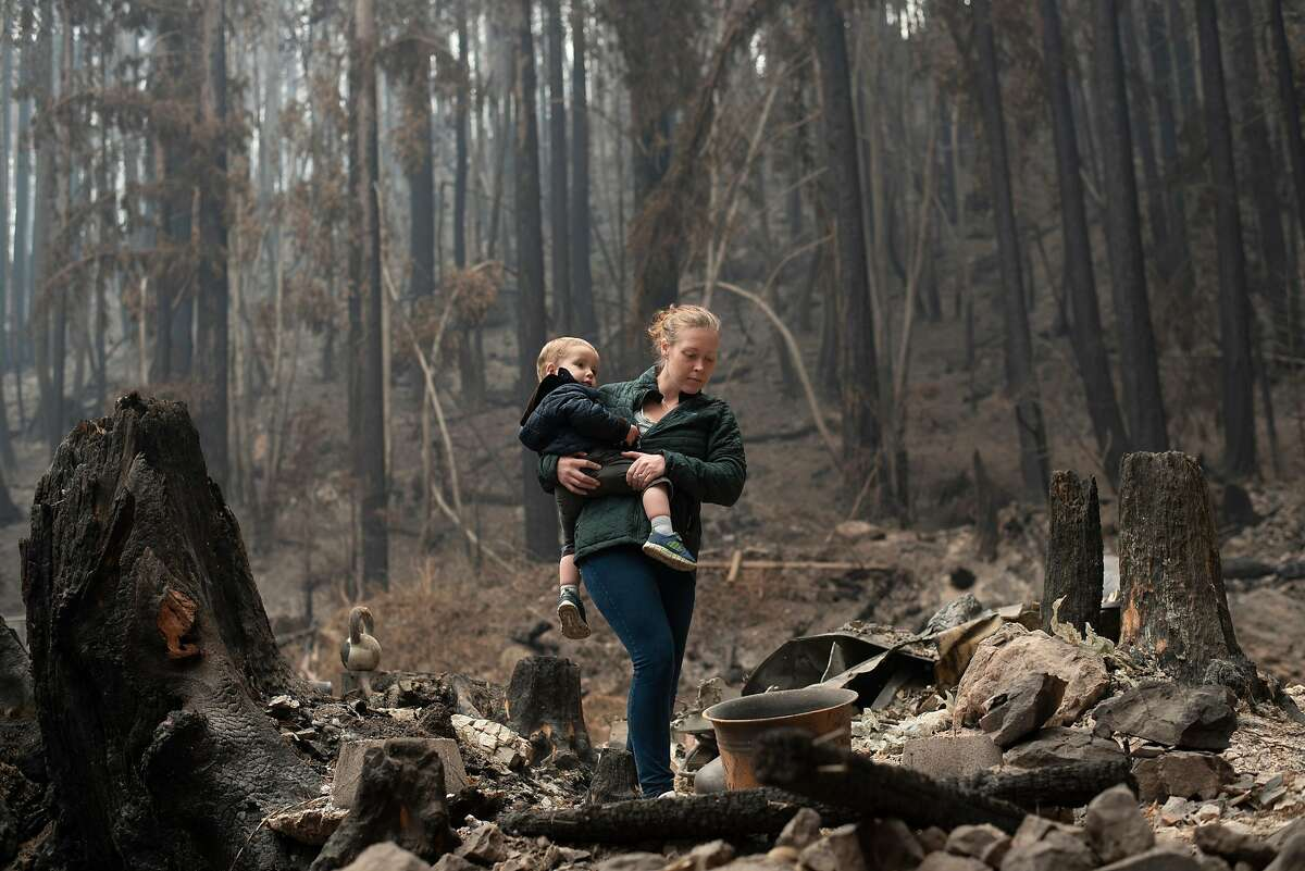 Allegra Keller holds her 20-month-old son Cristian as she walks through the wreckage of their home on Last Chance Road in Davenport on Sept. 11, 2020. Allegra Keller's husband Geoffrey Keller is a Cal Fire fighter and was on duty when she got the call to evacuate. His captain let him off the shift and he raced to meet her. They grabbed their things and left behind the small cabin he built for them when they married in 2017.