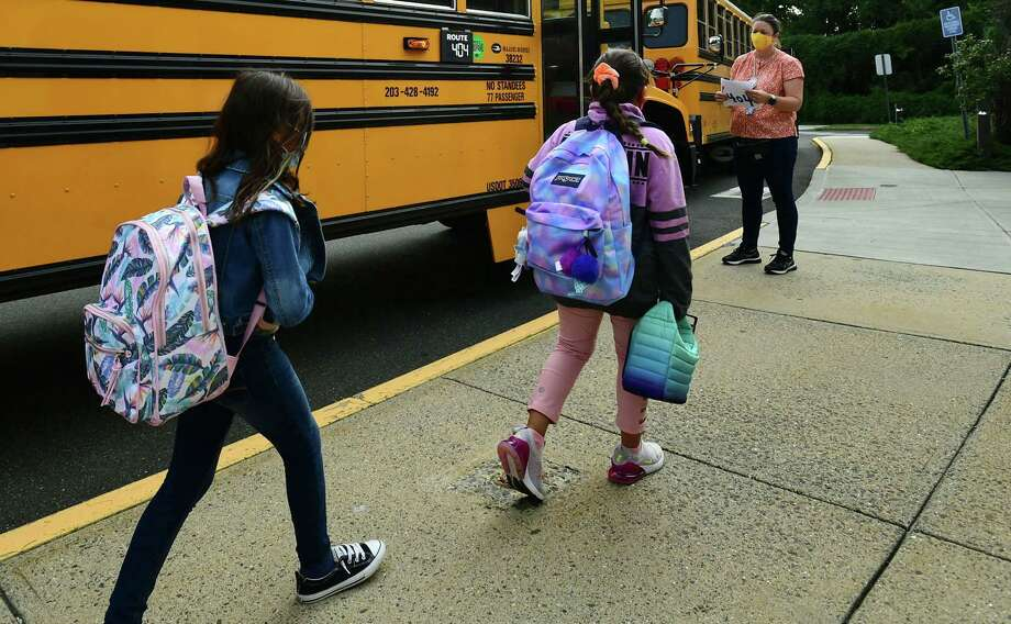 Bus monitors help students board buses at Fox Run Elementary School Thursday, September 16, 2020. Norwalk Public Schools is working out the kinks in their bussing after adding bus monitors to help enforce COVID guidelines. To do this, the district is keeping on their seasonal help in the Transportation Department until October. Photo: Erik Trautmann / Hearst Connecticut Media / Norwalk Hour