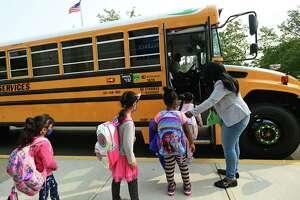 School staff help students boarding buses at Fox Run Elementary School Thursday, September 16, 2020.