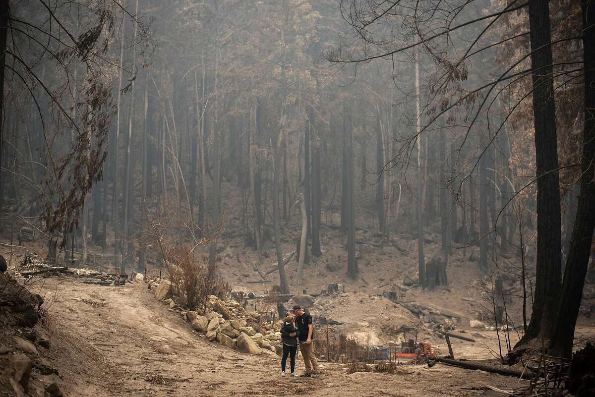 Cal Fire fighter Geoffrey Keller, his wife Allegra Keller and their 20-month-old son Cristian stop for a quiet moment in front of what remains of their home at the end of Last Chance Road in Davenport after the CZU Lightning Complex Fire swept through, Sept. 11, 2020. The 29-year-old was battling a fire when he received a frantic call from his wife that she was going to evacuate. His captain let him off the shift and he raced to meet her. They grabbed their things and left behind the small cabin he built for them when they married in 2017.