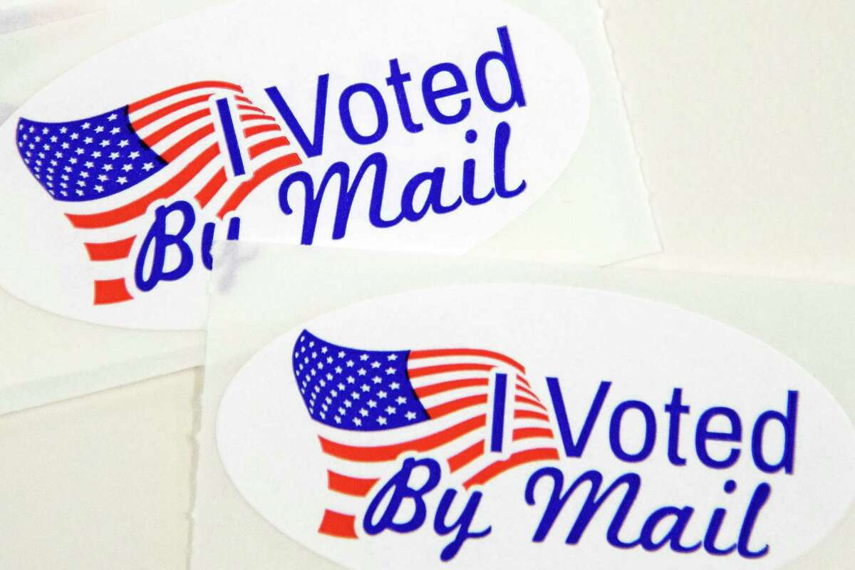 """TOPSHOT - Stickers that read """"I Voted By Mail"""" sit on a table waiting to be stuffed into envelopes by absentee ballot election workers at the Mecklenburg County Board of Elections office in Charlotte, NC on September 4, 2020. - The US election is officially open: North Carolina on September 4, 2020 launched vote-by-mail operations for the November 3 contest between President Donald Trump and Joe Biden, which is getting uglier by the day. Worries about the unabated spread of the coronavirus are expected to prompt a major increase in the number of ballots cast by mail, as Americans avoid polling stations. (Photo by Logan Cyrus / AFP) (Photo by LOGAN CYRUS/AFP via Getty Images)"""