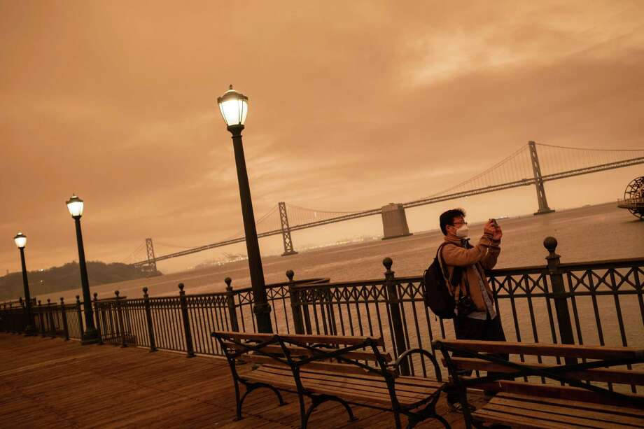 A man takes a photo along the Embarcadero last week in San Francisco as the city and region were blanketed in a haze from the wildfires. Photo: Photo By Nick Otto For The Washington Post / For The Washington Post