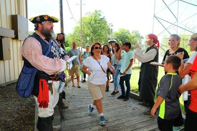 During a previous year's Magnolia Stroll event, Rosett Valasco visting from California dances her way a cross the foot bridge, guarded by pirates.