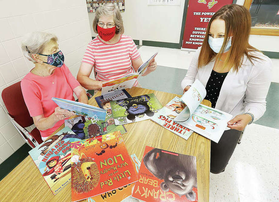 Ruth Wolter, left, head of the book club club at Resurrection Lutheran Church in Godfrey, and Kay Tucker, center, church treasurer, look over some of the books that a donation of more than $1,500 from the church could buy for students at Gilson Brown Elementary School in Godfrey. Kindergarten teacher Carey Cappel, right, joined them Tuesday after the money was presented. The funds will allow all of the school's 175 students to receive one book a month