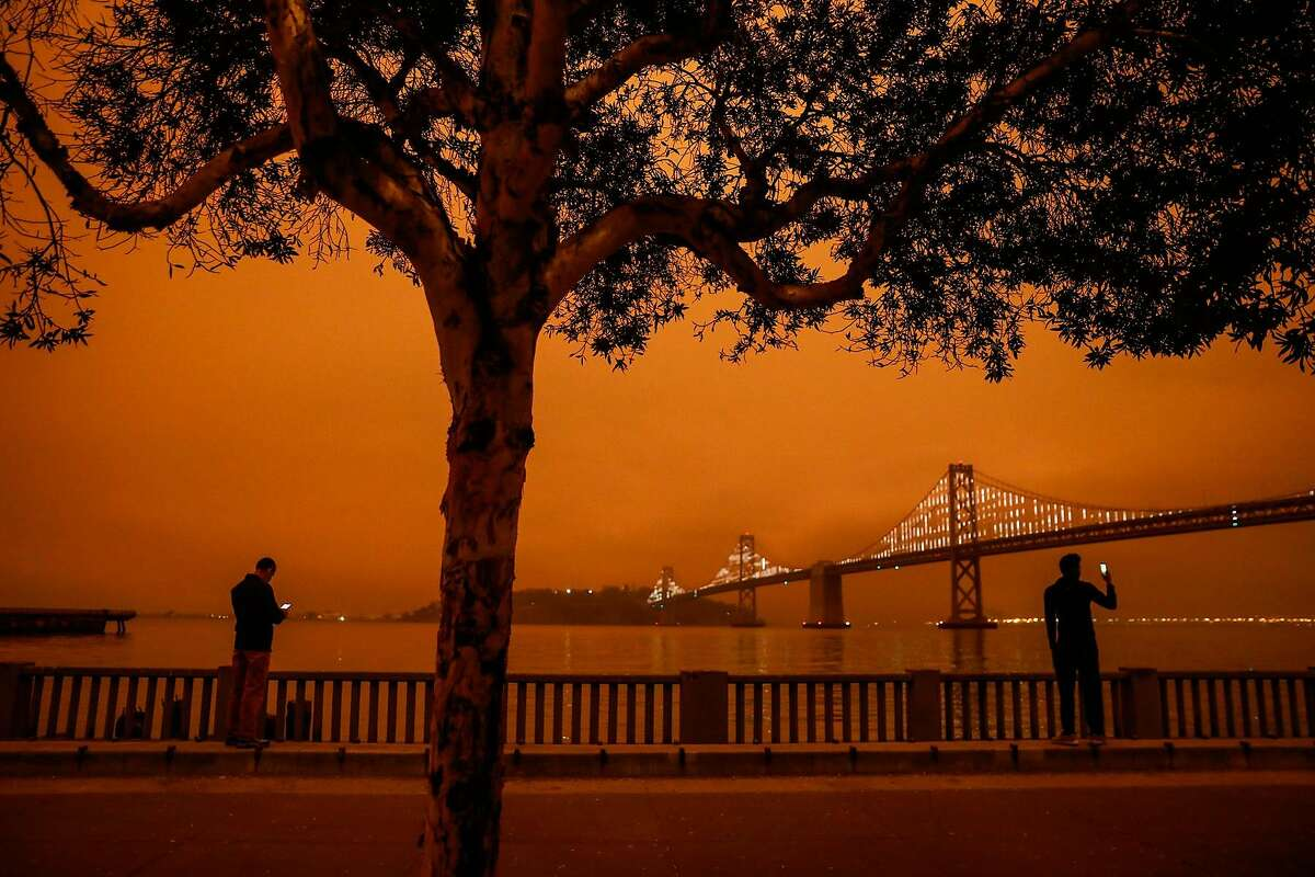Juan Marmol (left) and another man take footage of the sky next to the Bay Bridge as dark orange skies hang over downtown San Francisco, Calif. Wednesday, September 9, 2020 due to multiple wildfires burning across California and Oregon.