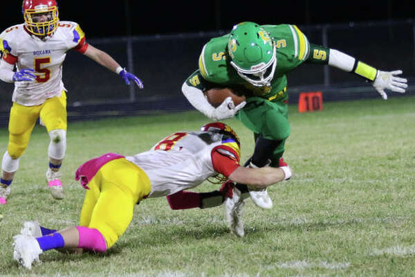 Roxana's Braeden Wells (left) shoots in to take Southwestern running back Gavin Day down a 2019 football game at Knapp Field in Piasa. Prep football has been postponed by the IHSA to next spring because of the COVID-19 pandemic.