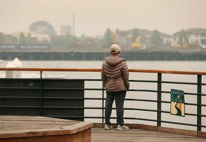 The Alameda shoreline is barely visible across the Oakland Estuary for a man standing at Jack London Square in Oakland on Sept. 10.