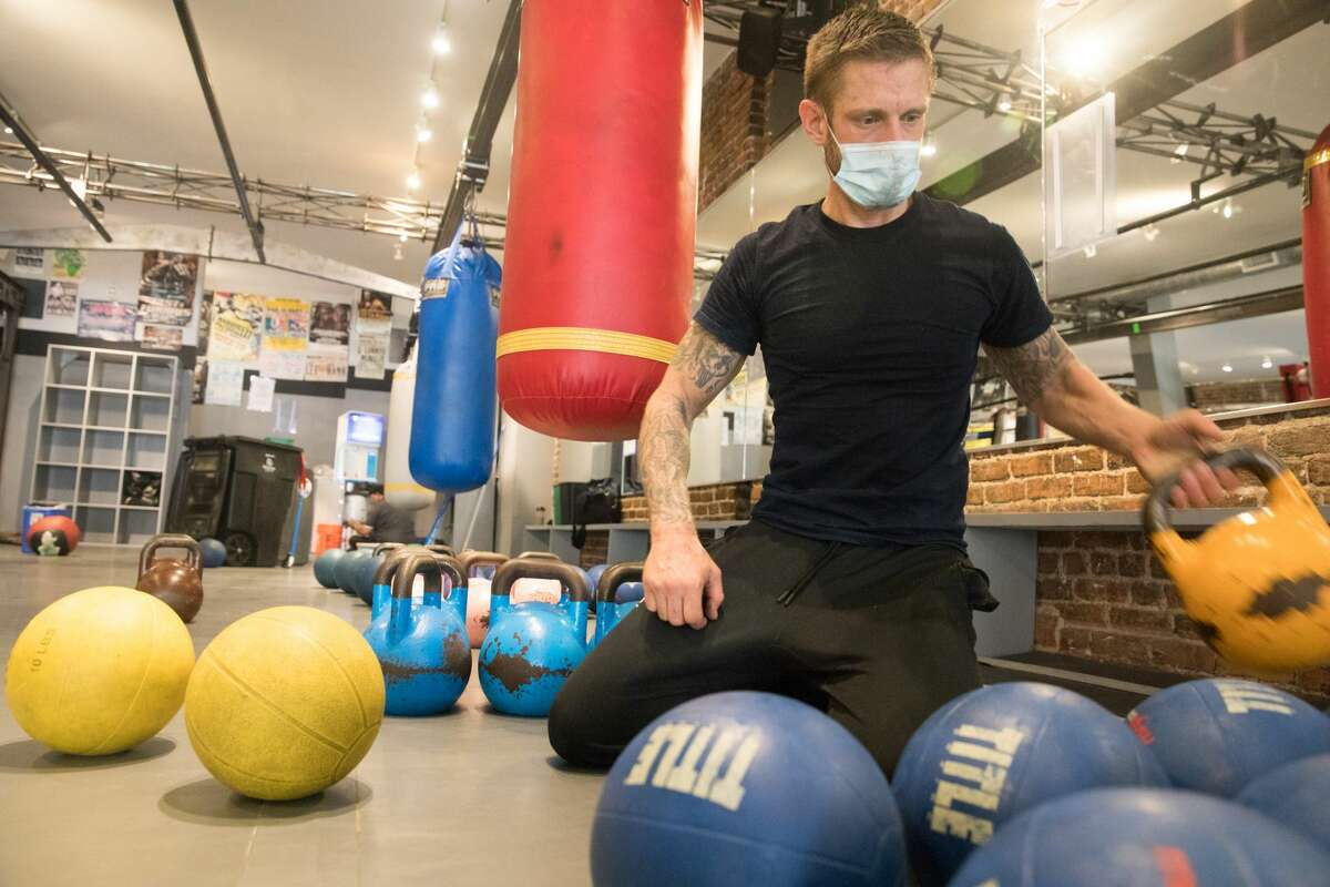Hit Fit SF employee Sean Mason places medicine balls and kettlebells at its Sutter Street location in San Francisco on Sept. 16, 2020. Owner Simon Redmond and his employees fix up his gym to make it compliant for city's new indoor capacity rules due to the COVID-19 coronavirus pandemic.