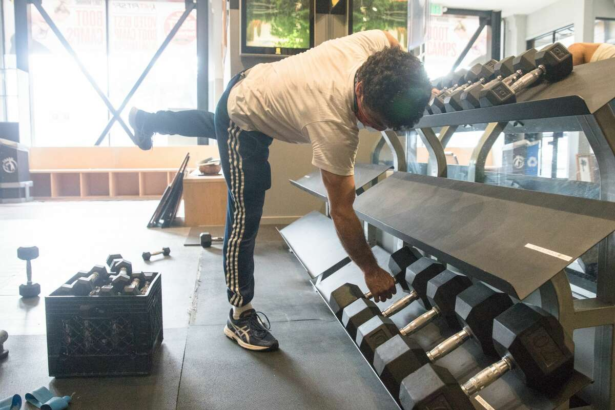 Hit Fit SF employee Aldolfo Velez places free weights on a stand at its Sutter Street location in San Francisco on Sept. 16, 2020. Owner Simon Redmond and his employees fix up his gym to make it compliant for city's new indoor capacity rules due to the COVID-19 coronavirus pandemic.