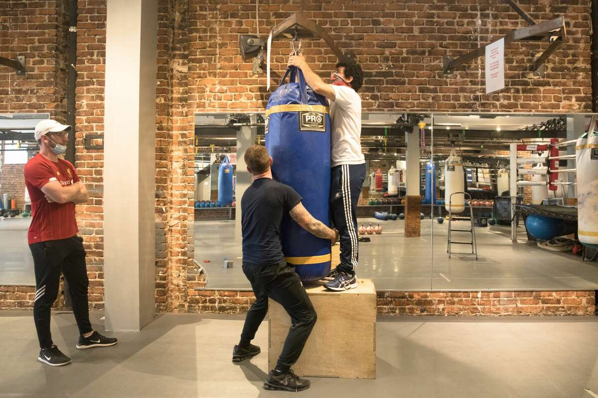 Hit Fit SF employees (right to) Aldolfo Velez and Sean Mason hang a punching bag as Wayne Squires look on at the gym's Sutter Street location in San Francisco, California on Sept. 16, 2020.
