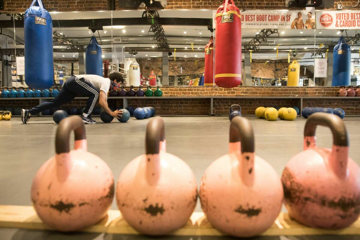 Hit Fit SF employee Aldolfo Velez moves medicine balls and kettlebells at its Sutter Street location in San Francisco on Sept. 16, 2020. Owner Simon Redmond and his employees fix up his gym to make it compliant for city's new indoor capacity rules due to the COVID-19 coronavirus pandemic.