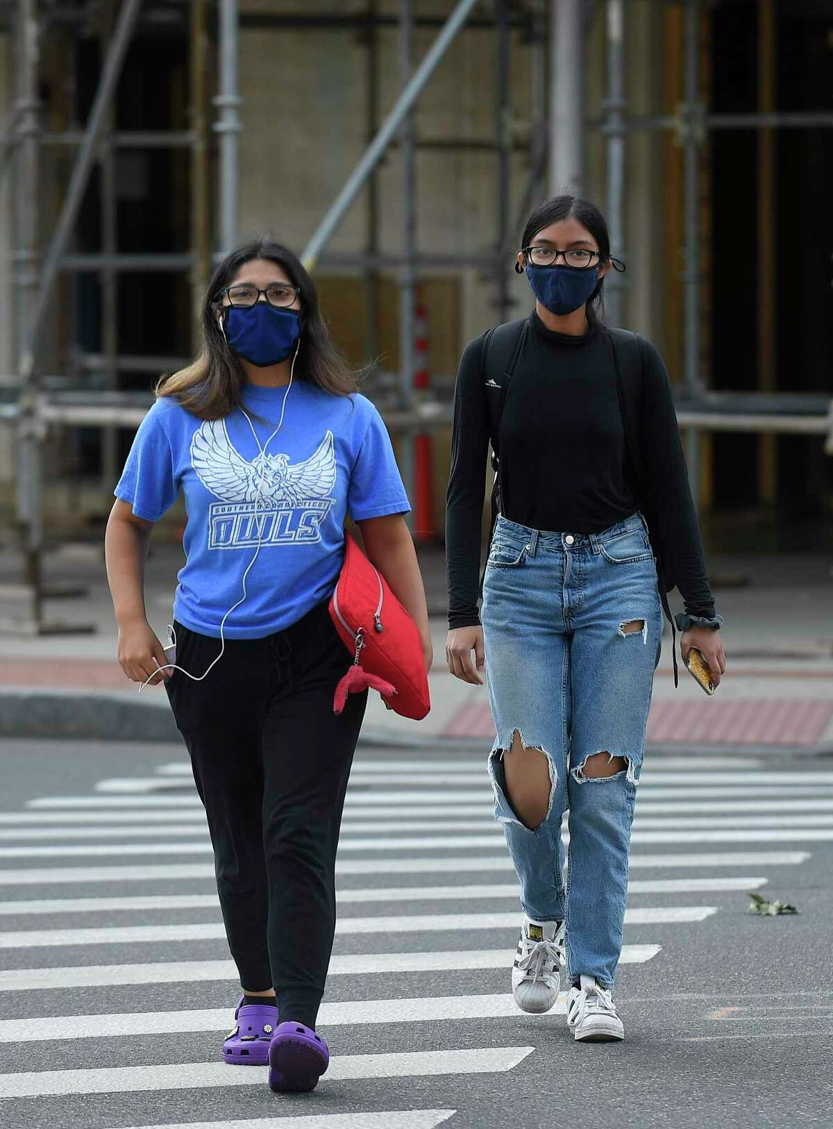 Young people wear masks as they walk through the downtown business district on Sept. 16, 2020 in Stamford, Connecticut.