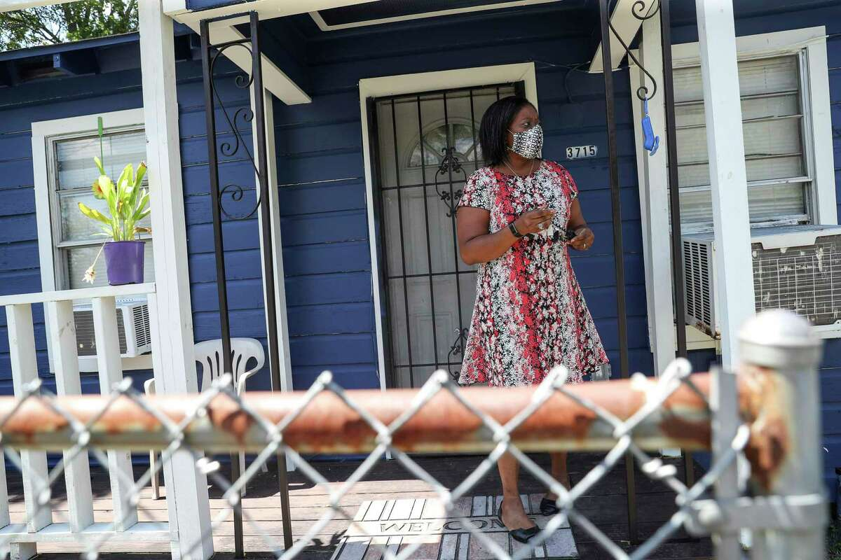 """Regina Martin-Morgan walks out of her house Tuesday, Sept. 15 2020, at her house in Houston. Martin-Morgan lost both of her parents to cancer, and her brother's cancer is in remission. She is one of dozens of plaintiffs in a wrongful death lawsuit against Union Pacific over legacy rail yard contamination. Last year, Texas health officials identified a cancer cluster in the area near the contamination. """"It's a different world when you lose both of your parents,"""" she said. """"It's really something that'll take the life out of you."""""""