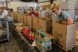 Volunteers assemble boxes of food for senior citizens at the Southeast Texas Food Bank on March 18, 2020. The food bank puts together 2500 of these boxes every month. These volunteers put these packages together every Tuesday, Wednesday, and Friday afternoon. Fran Ruchalski/The Enterprise
