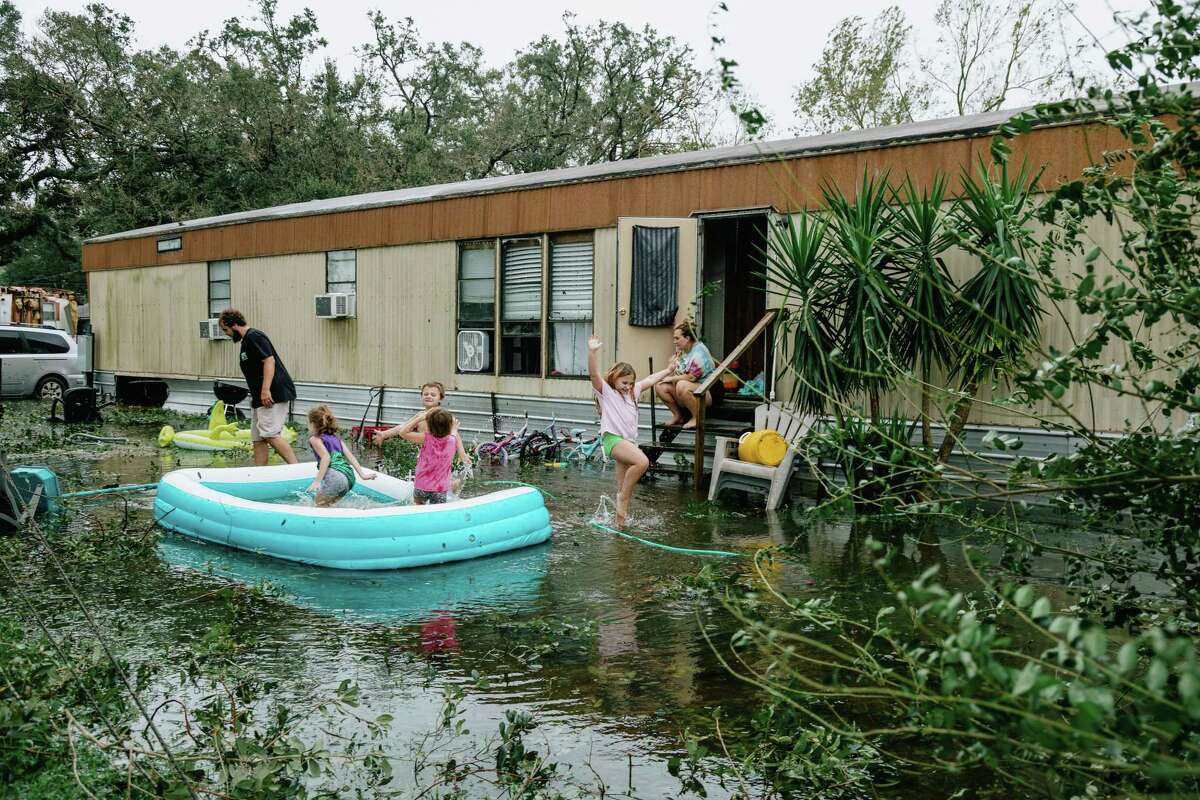 Clinton and Randal Ream with their son Saylor and daughter Nayvie and two neighbors, Aubrey Miller and Harmony Morgan, at their home in West Pensacola. Officials in Escambia County, which includes Pensacola, said emergency crews rescued 377 people. A curfew is in effect for the next three days.
