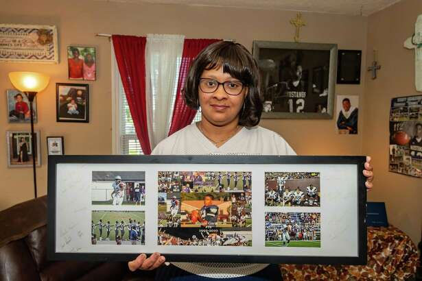 JoAnn Parkinson stands in her living room with a collection of photos from her son's high school days surrounded by photos of her family. Reggie Garrett, Jr. passed away in his senior year from an undiagnosed cardiac condition on September 17, 2010 playing the game he loved for the West Orange-Stark Mustangs. Photo made on September 16, 2020. Fran Ruchalski/The Enterprise