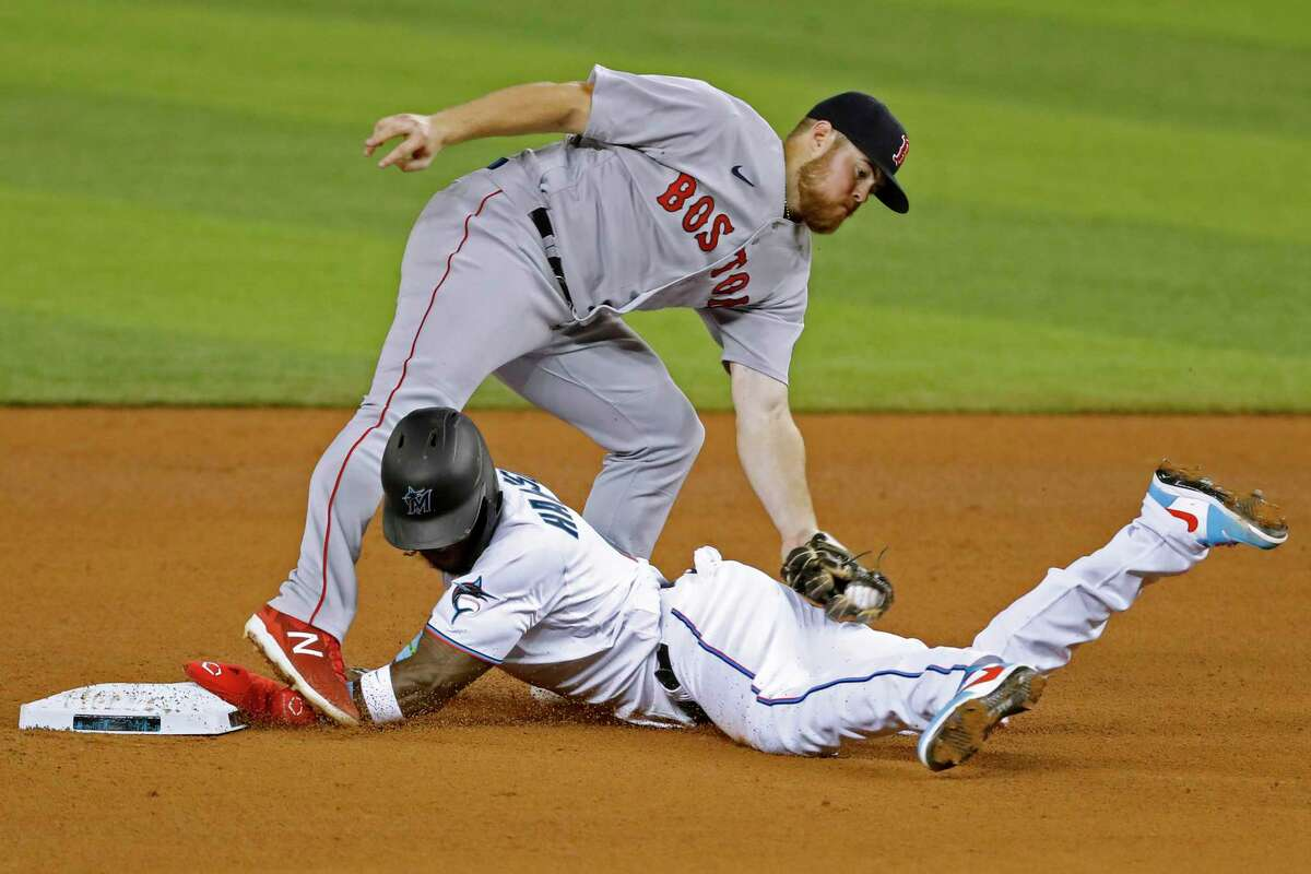 MIAMI, FLORIDA - SEPTEMBER 16: Monte Harrison #4 of the Miami Marlins safely steals second base past the tag of Christian Arroyo #39 of the Boston Red Sox during the fourth inning at Marlins Park on September 16, 2020 in Miami, Florida. (Photo by Michael Reaves/Getty Images)