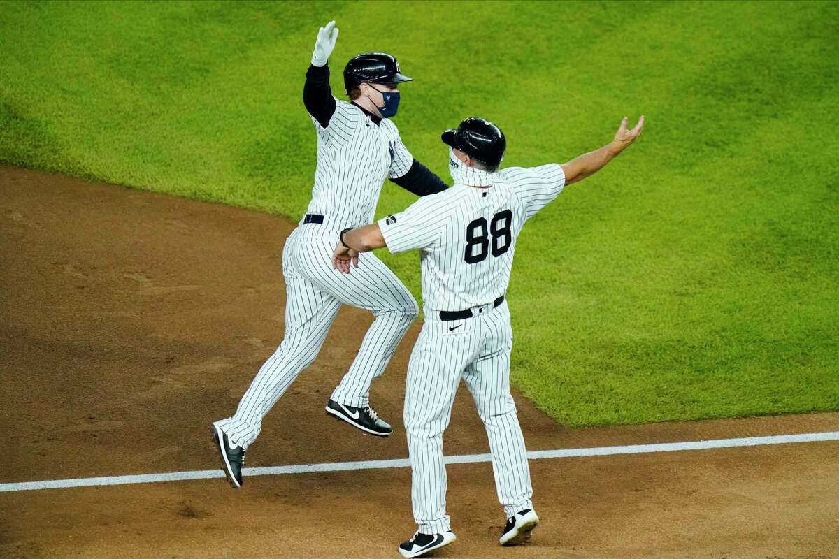 New York Yankees' Clint Frazier, left, celebrates with third base coach Phil Nevin after hitting a home run during the fourth inning of a baseball game against the Toronto Blue Jays Wednesday, Sept. 16, 2020, in New York. (AP Photo/Frank Franklin II)