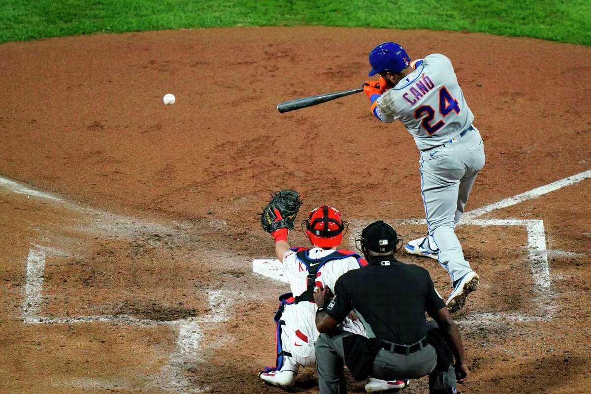 New York Mets' Robinson Cano hits a run-scoring ground out off Philadelphia Phillies pitcher Zack Wheeler during the fourth inning of a baseball game, Wednesday, Sept. 16, 2020, in Philadelphia. (AP Photo/Matt Slocum)