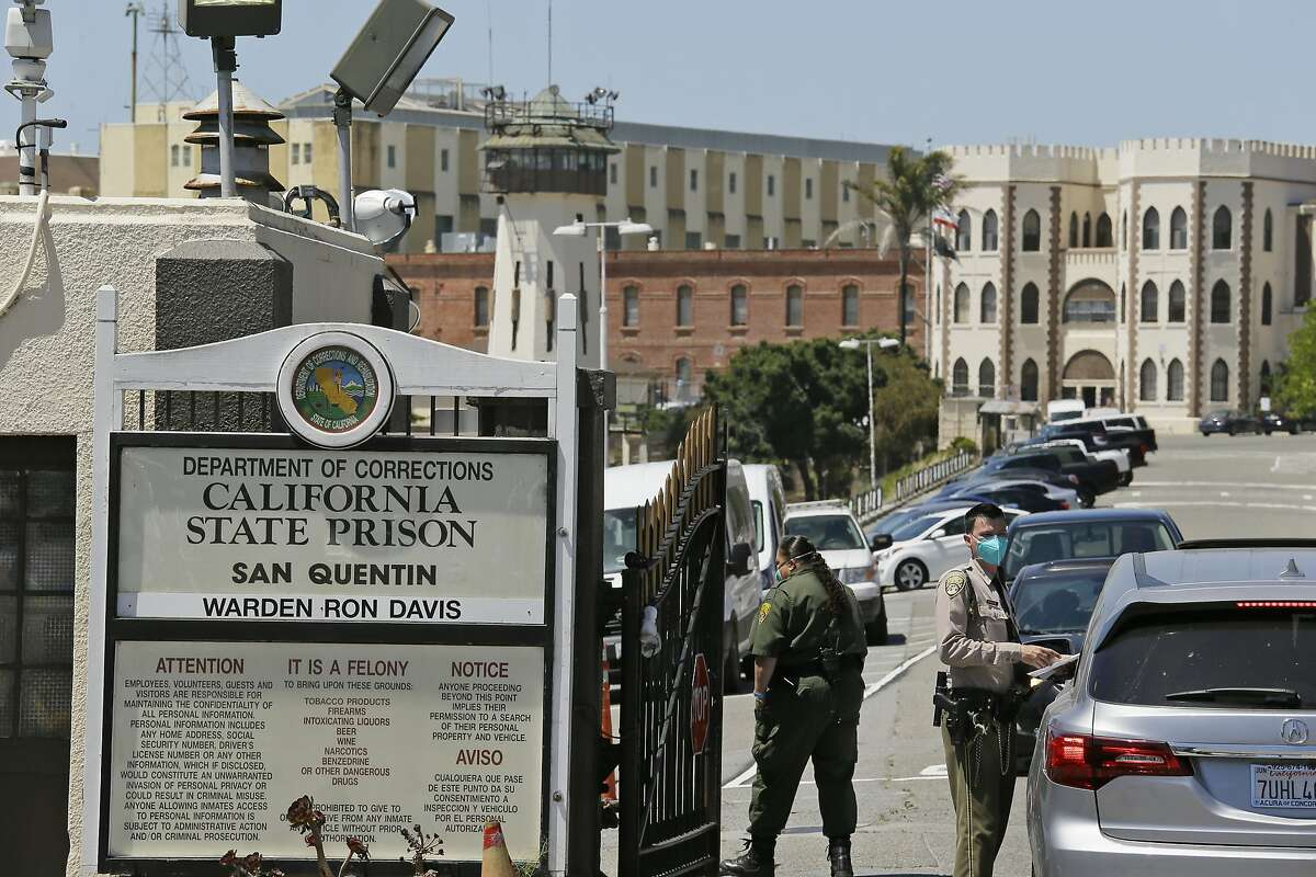 FILE - In this July 9, 2020, file photo, a correctional officer checks a car entering the main gate of San Quentin State Prison in San Quentin, Calif. California has launched a $30 million program to provide thousands of parolees with community services after they complete their prison sentences or are released months early because of the coronavirus pandemic, officials announced Thursday, Aug. 27, 2020. (AP Photo/Eric Risberg, File)